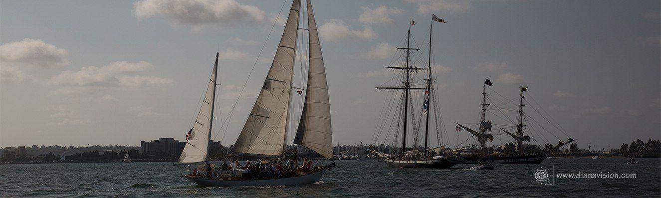 San Diego Tall Ship Festival - JADA at full sails - a charter sailboat - by a tall ship